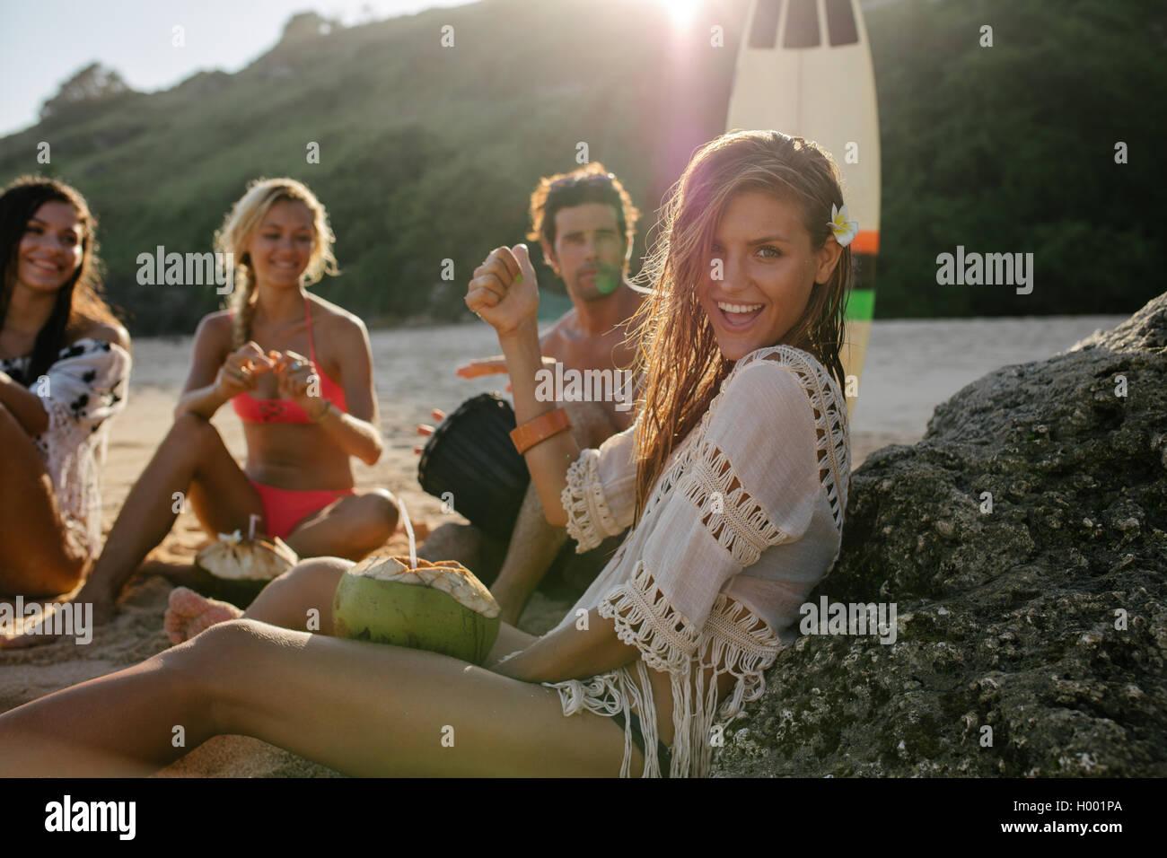Emocionada joven divirtiéndose en la playa con sus amigos en el fondo. Grupo de amigos disfrutando de sus vacaciones Imagen De Stock