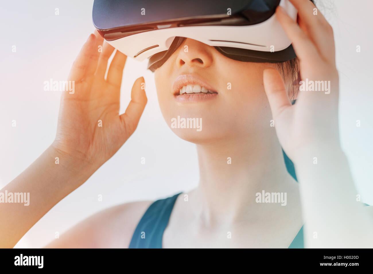 Primer plano de la mujer asiática con el casco de realidad virtual y apartar la mirada. Hembra que lleva puestas Imagen De Stock