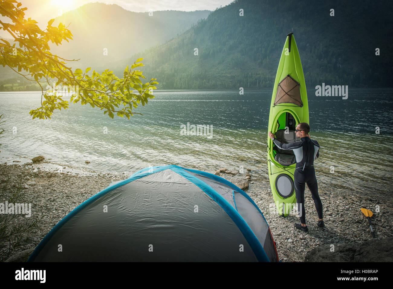 Tour de Kayak Preparación. Los hombres caucásicos con su kayak y Lake Shore ubicado Tienda preparando Imagen De Stock