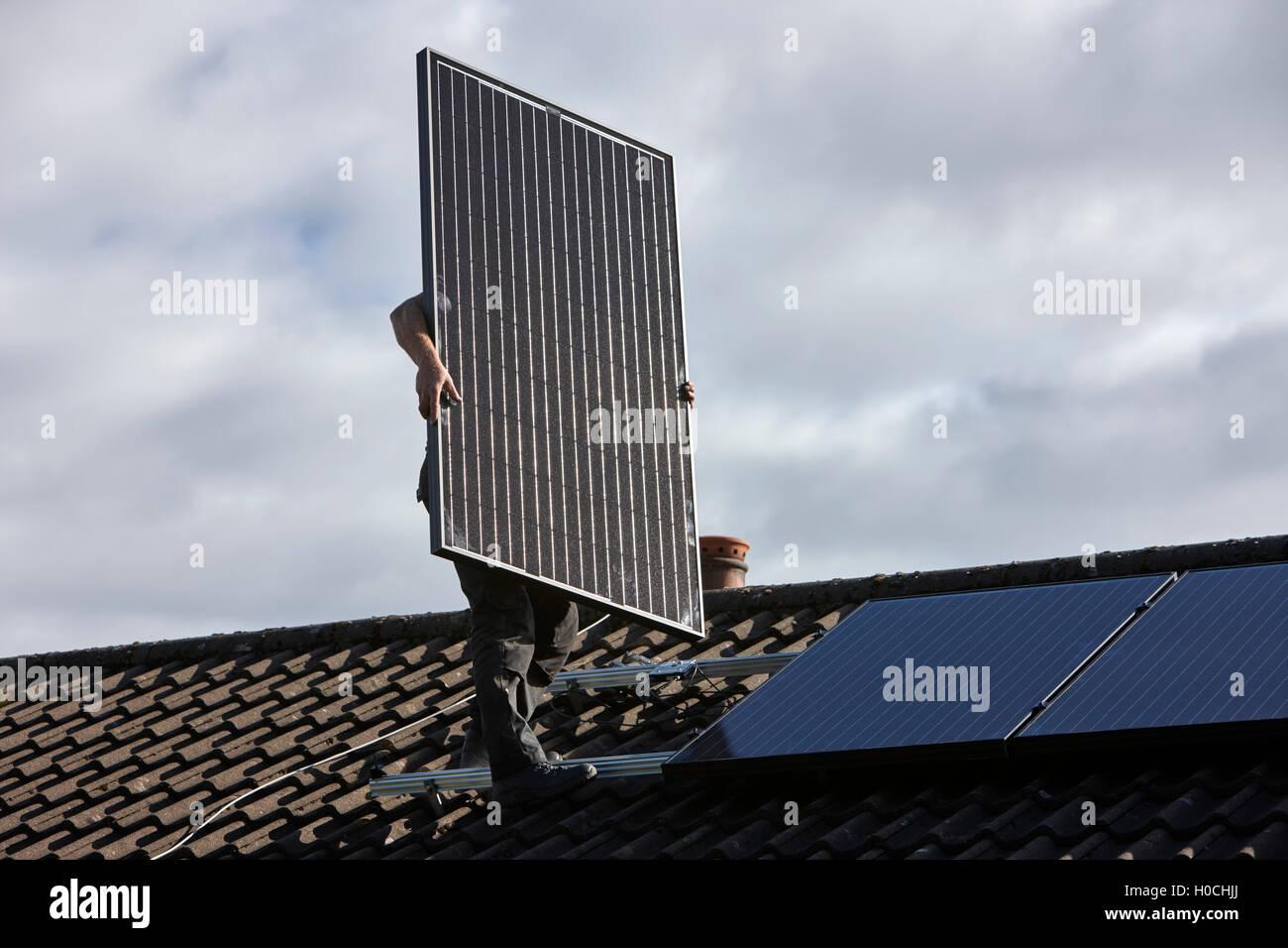 Hombre, la instalación de placas solares en la azotea en una instalación de panel solar doméstico Imagen De Stock