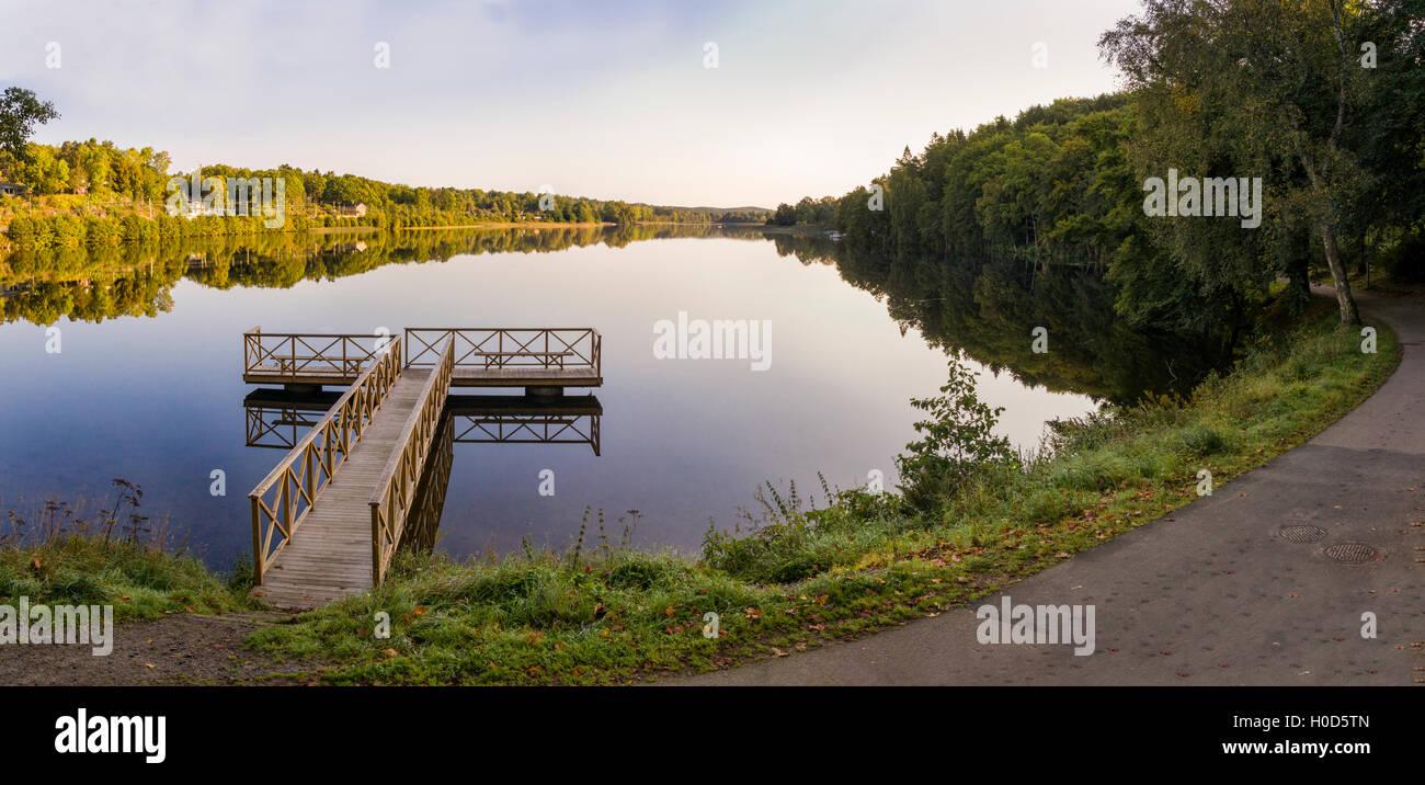 Temprano en la mañana paisaje paisaje de aguas tranquilas y el embarcadero de madera en el lago Sävelången, Floda, Foto de stock