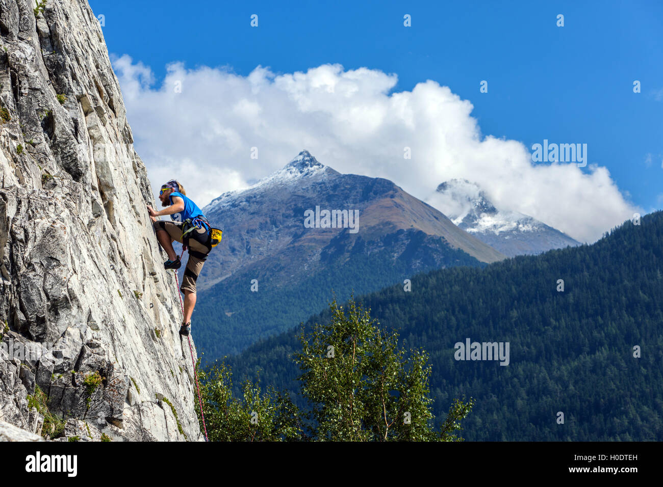 Slim escalador masculino en azul sobre roca escarpada, cielo azul con nubes y montañas Imagen De Stock