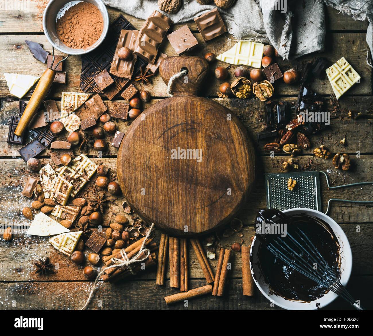 Piezas de blanco, oscuro y chocolate con leche, nueces, cacao en polvo, chocolate derretido y especias con placa Imagen De Stock