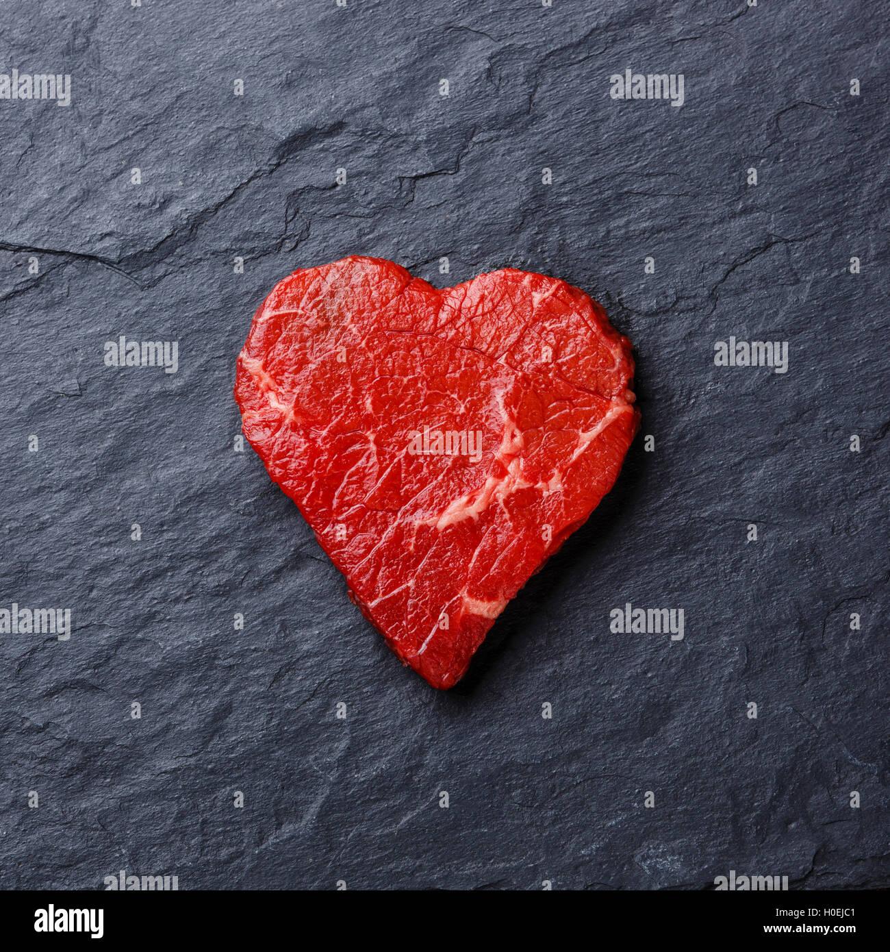 Carne fresca cruda forma de corazón sobre fondo de pizarra de piedra oscura Imagen De Stock
