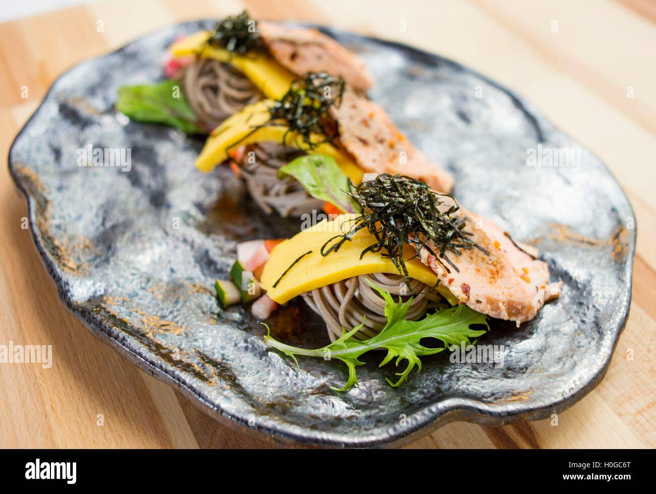 Salmón con fideos soba, hierbas y algas en plato negro Imagen De Stock