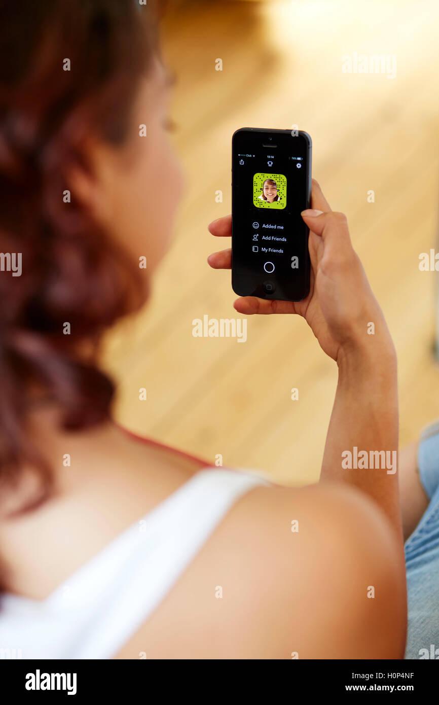 Chica utilizando Snapchat app en su iPhone Imagen De Stock