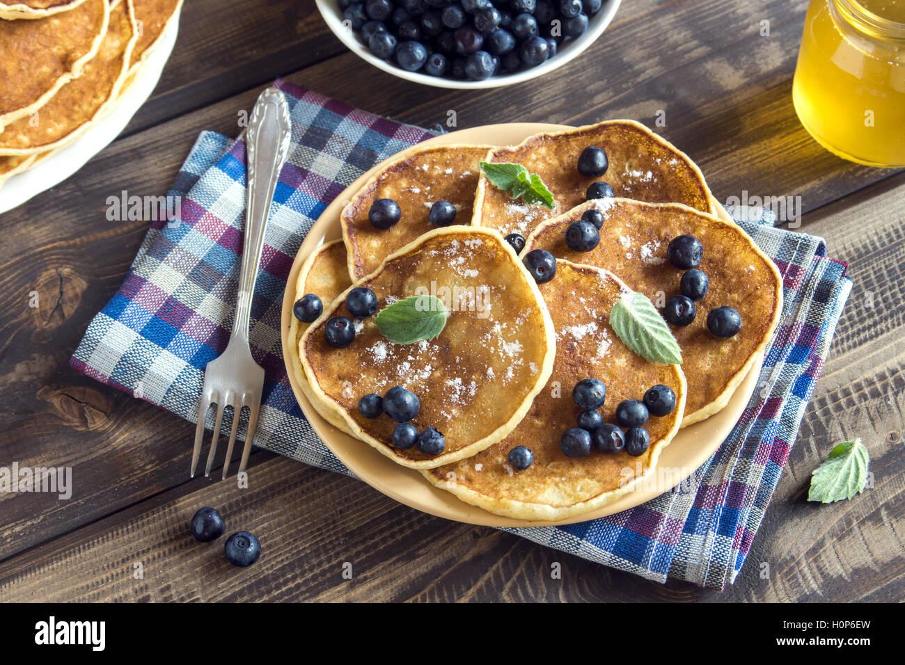 Los panqueques en la placa con los arándanos, menta y miel para el desayuno - comida vegetariana saludable Imagen De Stock