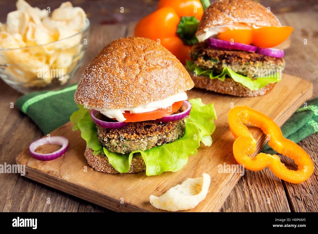 Hamburguesa de lentejas vegetariano con verduras sobre la tabla de cortar de madera - sabrosos y saludables bocadillos Foto de stock