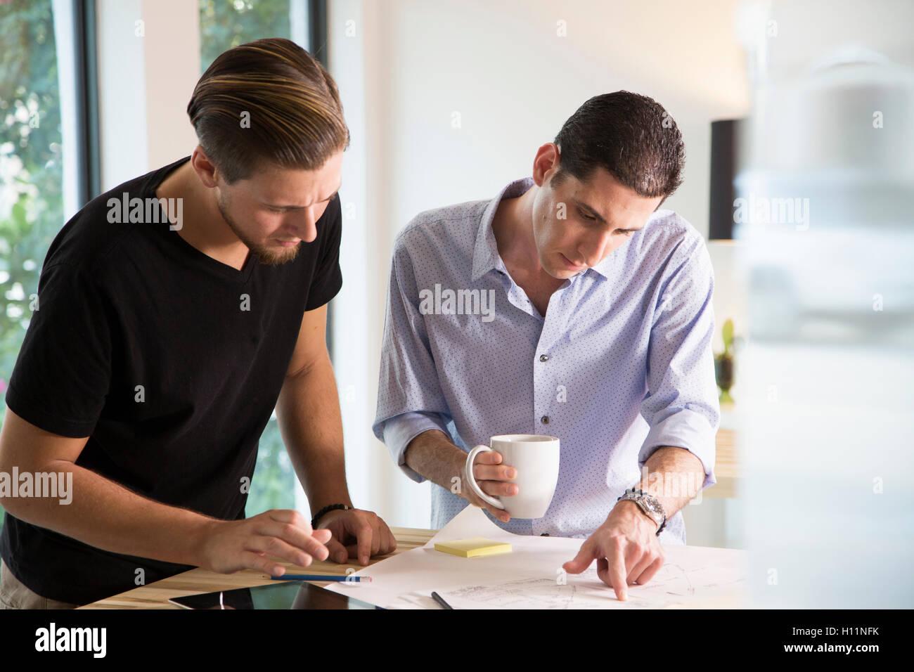 Dos hombres trabajadores de oficina compartir ideas en una moderna oficina Foto de stock