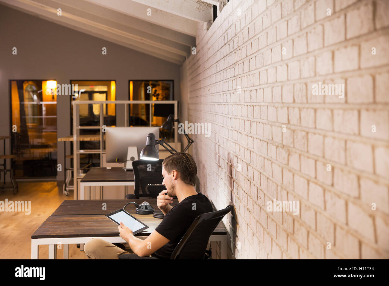 Jóvenes varones que trabajan solos en la oficina por la noche, él está usando una tableta digital. Foto de stock