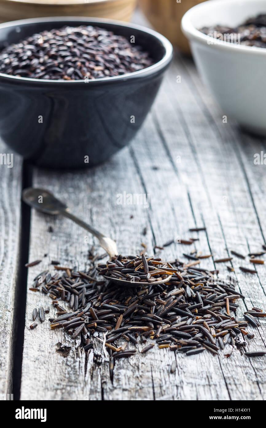 El arroz salvaje en una cuchara de mesa de madera antigua. Imagen De Stock