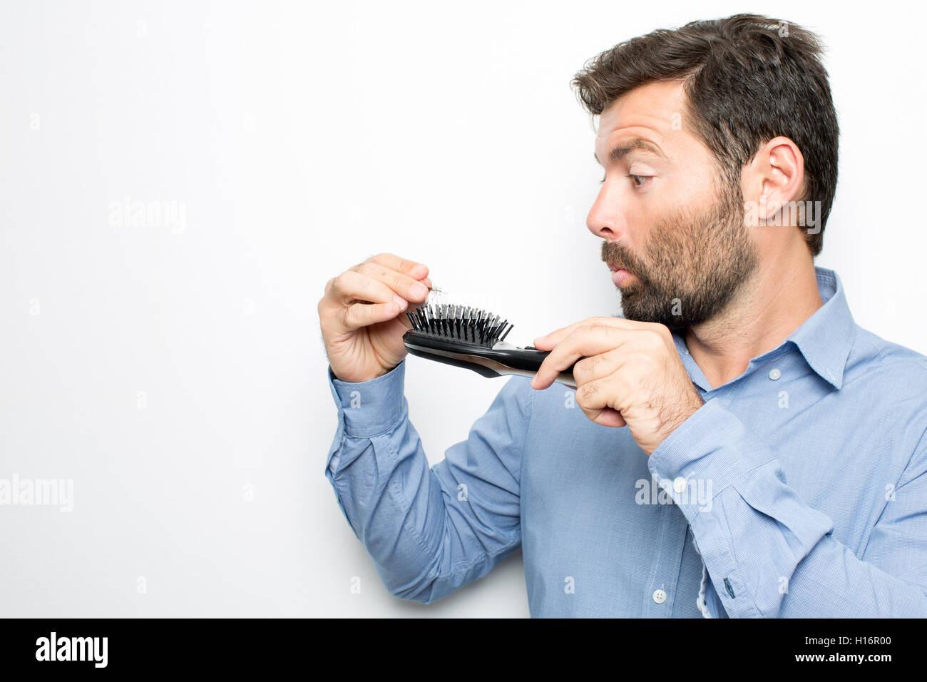 Hombre morena comprobando su cepillo perder el pelo Foto de stock