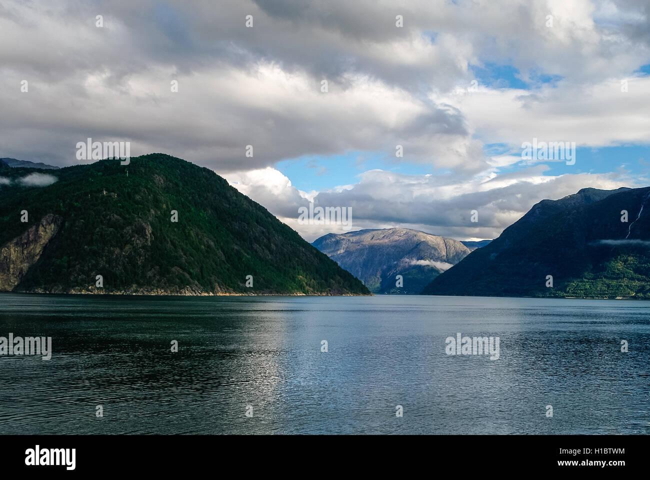 Cielo nublado sobre orillas del fiordo. Montañas con bosque verde, Eidfjord, Noruega Imagen De Stock