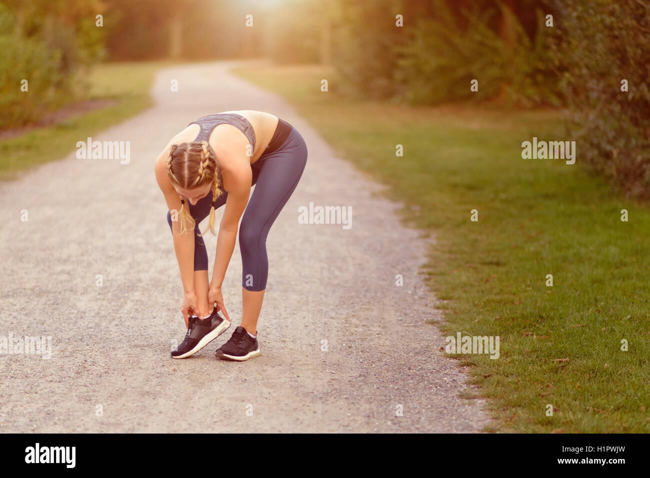 Mujer joven limbering arriba antes del entrenamiento haciendo ejercicios para estirar sus músculos en un país Imagen De Stock