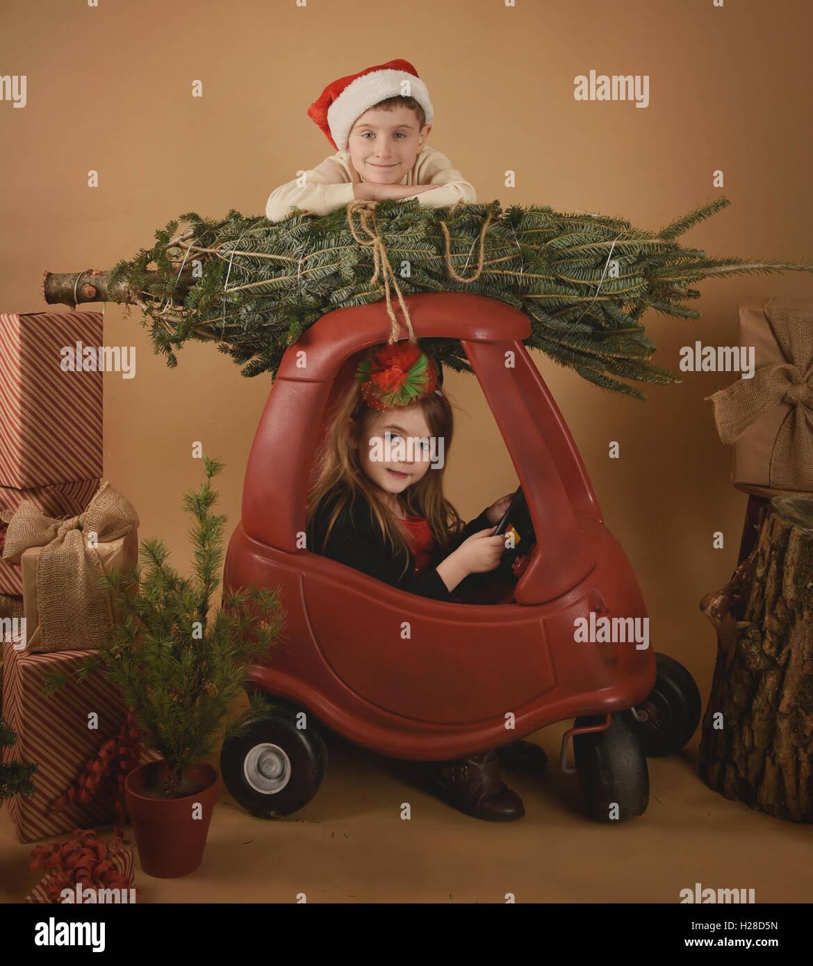 Dos niños están jugando a la Navidad en un estudio de fondo con un árbol y regalos de vacaciones Imagen De Stock