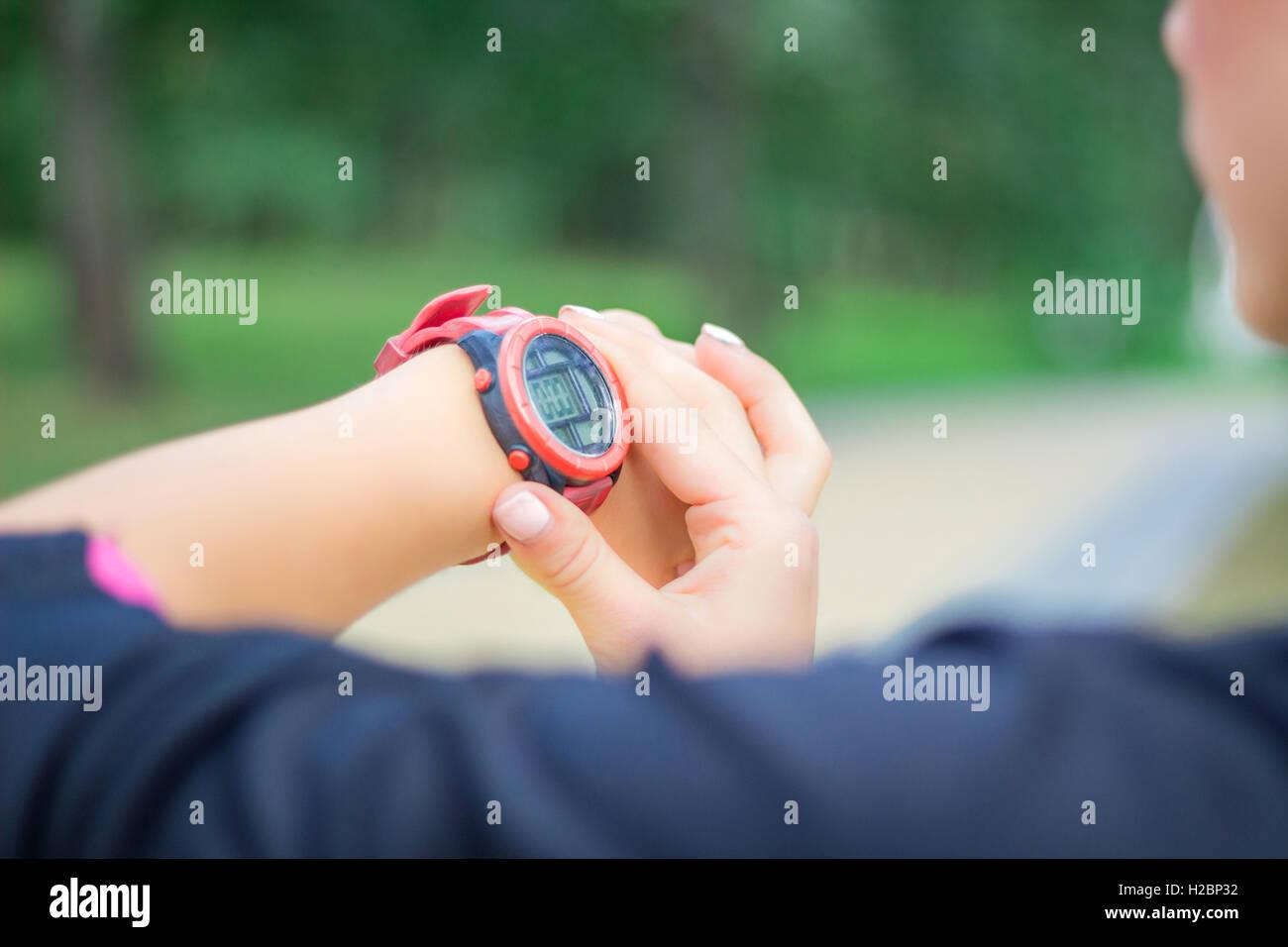 Joven chica fitness comprueba cronómetro tracker en su muñeca durante el funcionamiento de la piscina Imagen De Stock