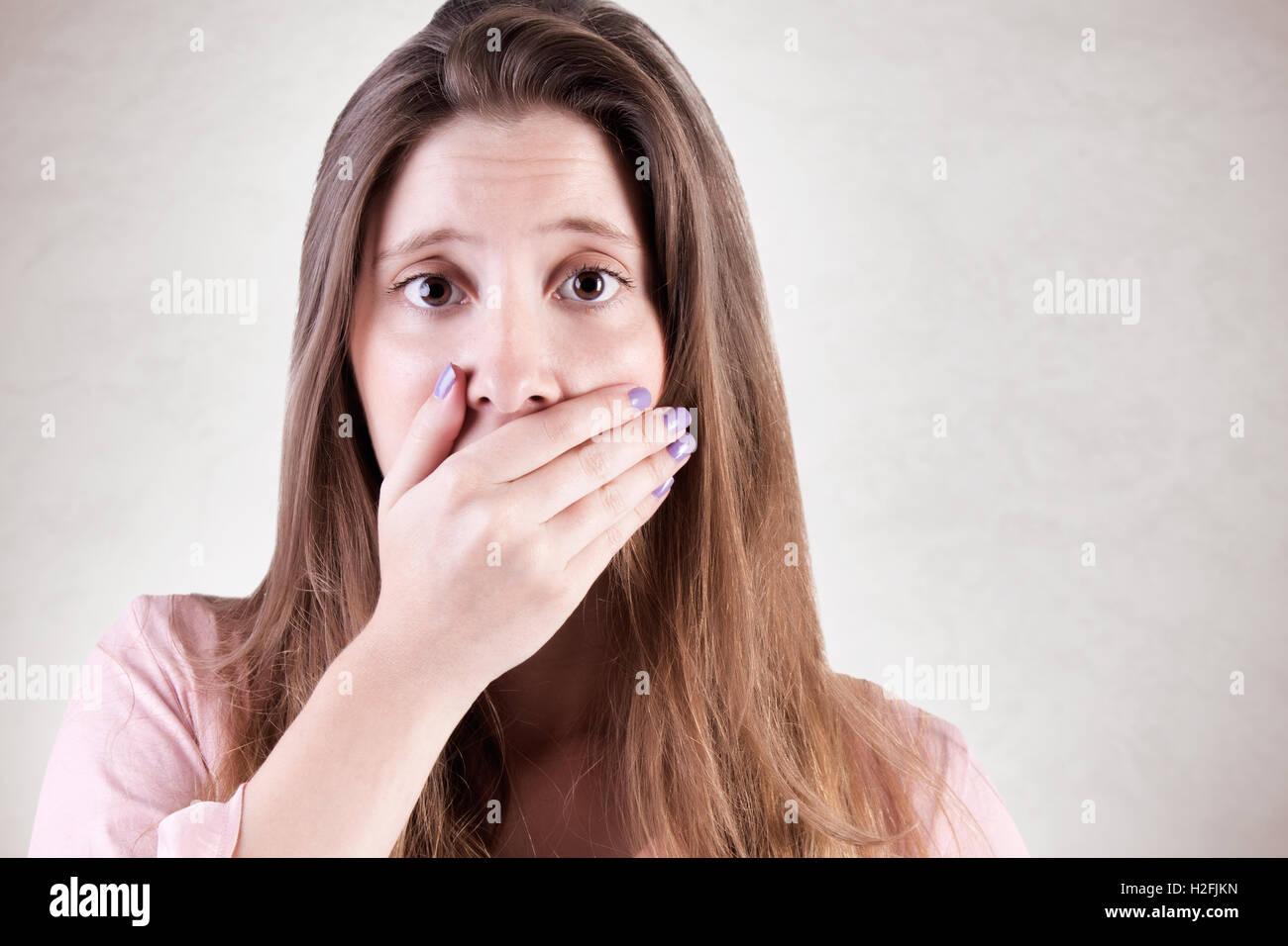 Primer plano de una mujer interesados cubriendo su boca, aislada en un estado de ánimo gris oscuro Imagen De Stock