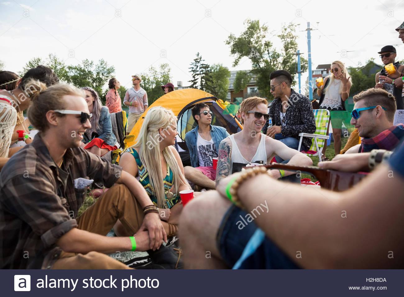 Jóvenes amigos colgar hacia fuera en el festival de música de verano camping Imagen De Stock