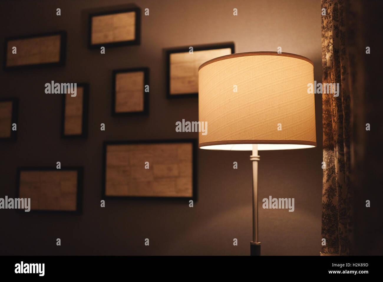 Una lámpara en un rincón oscuro de una habitación de hotel con cuadros abstractos fuera de foco en Imagen De Stock