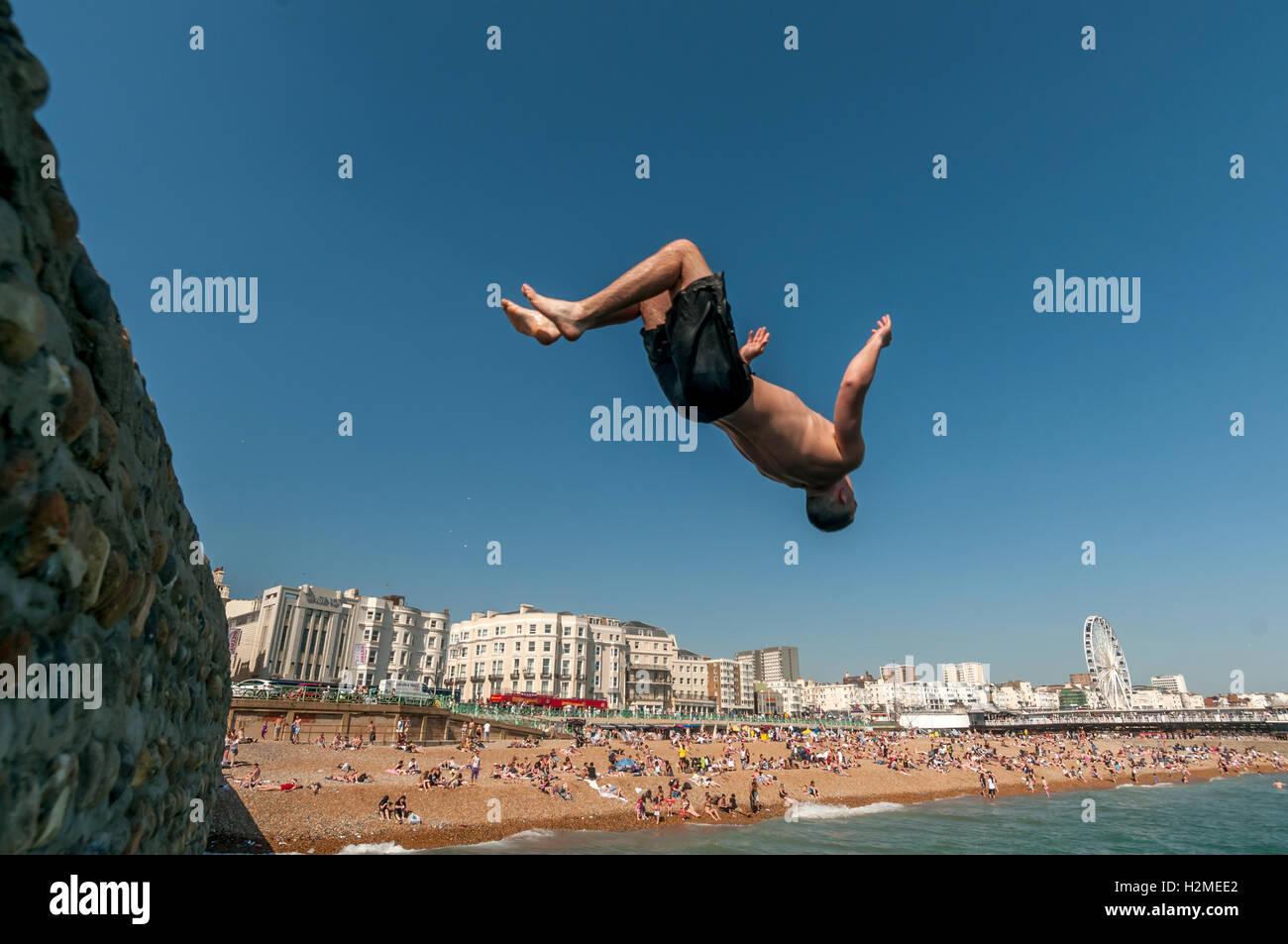 Los jóvenes saltando hacia el mar desde el espigón de banjo en Brighton Beach Imagen De Stock