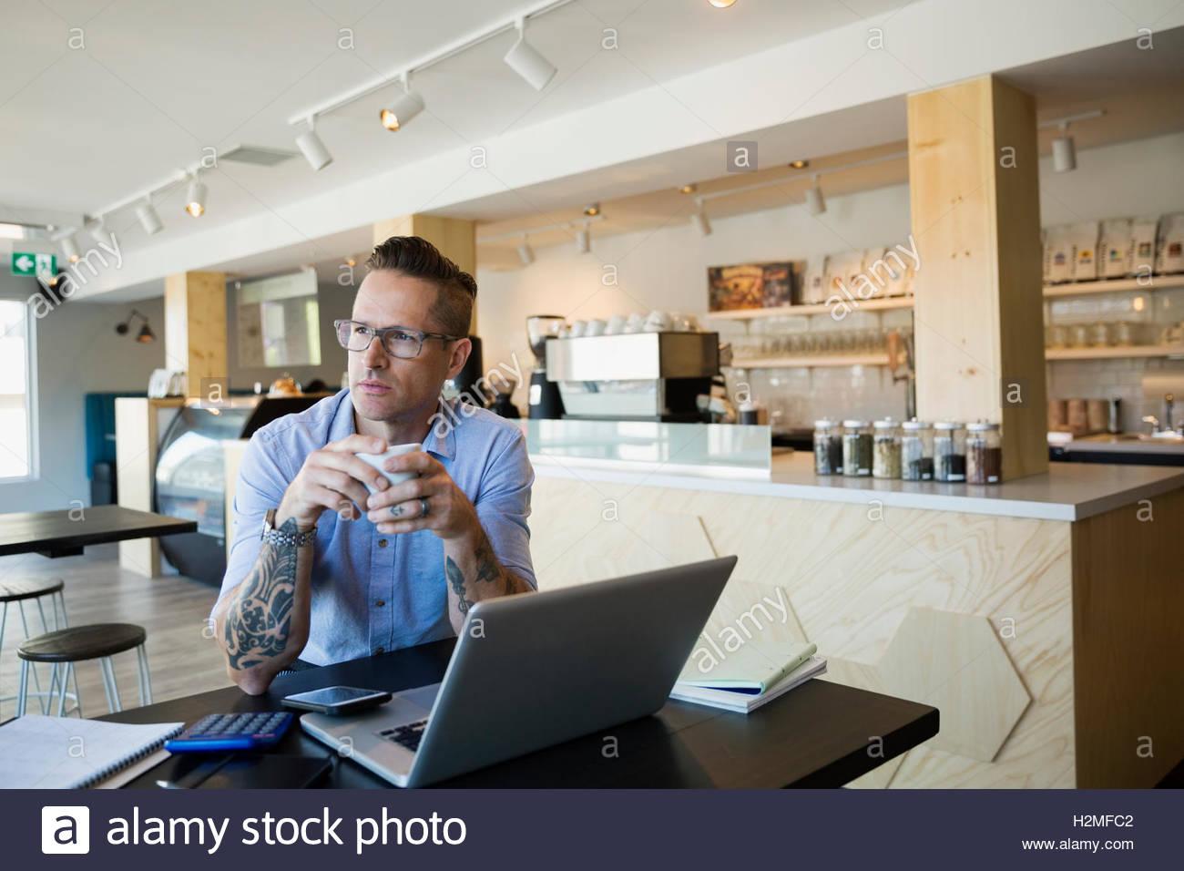 Pensativo cafe macho propietario beber café en portátil Imagen De Stock