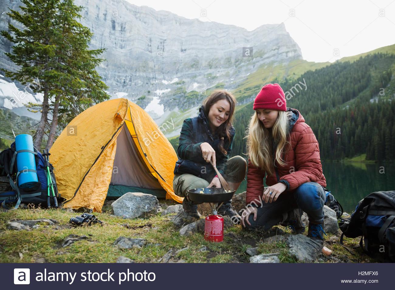 Amigas cocinar con la sartén sobre el queroseno estufa de camping en camping remoto Imagen De Stock