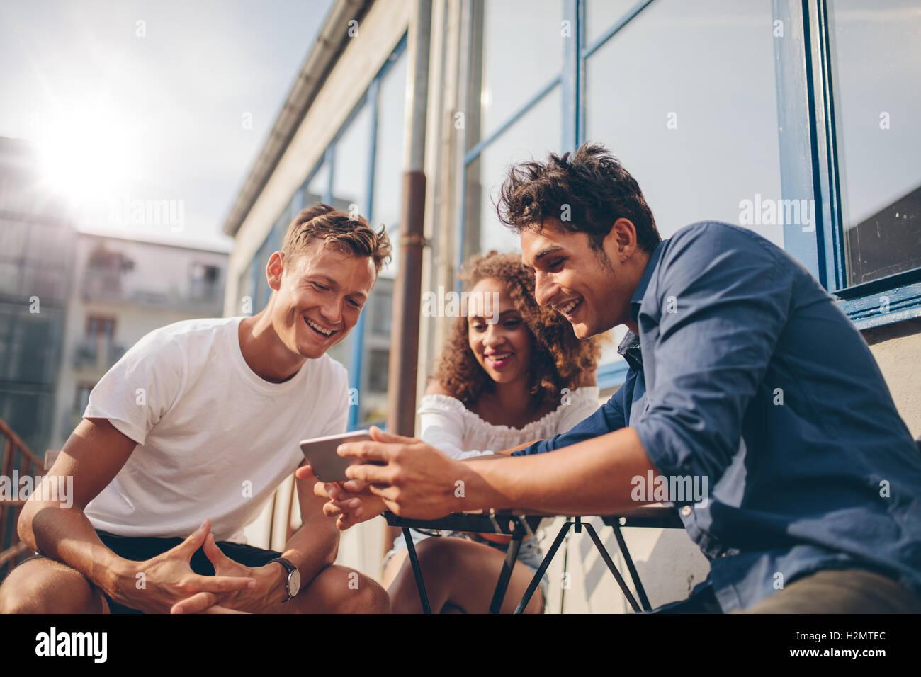 Tres jóvenes amigos sentados al aire libre y mirando al teléfono móvil. Grupo de gente sentada en la cafetería al aire libre y ver video en Foto de stock
