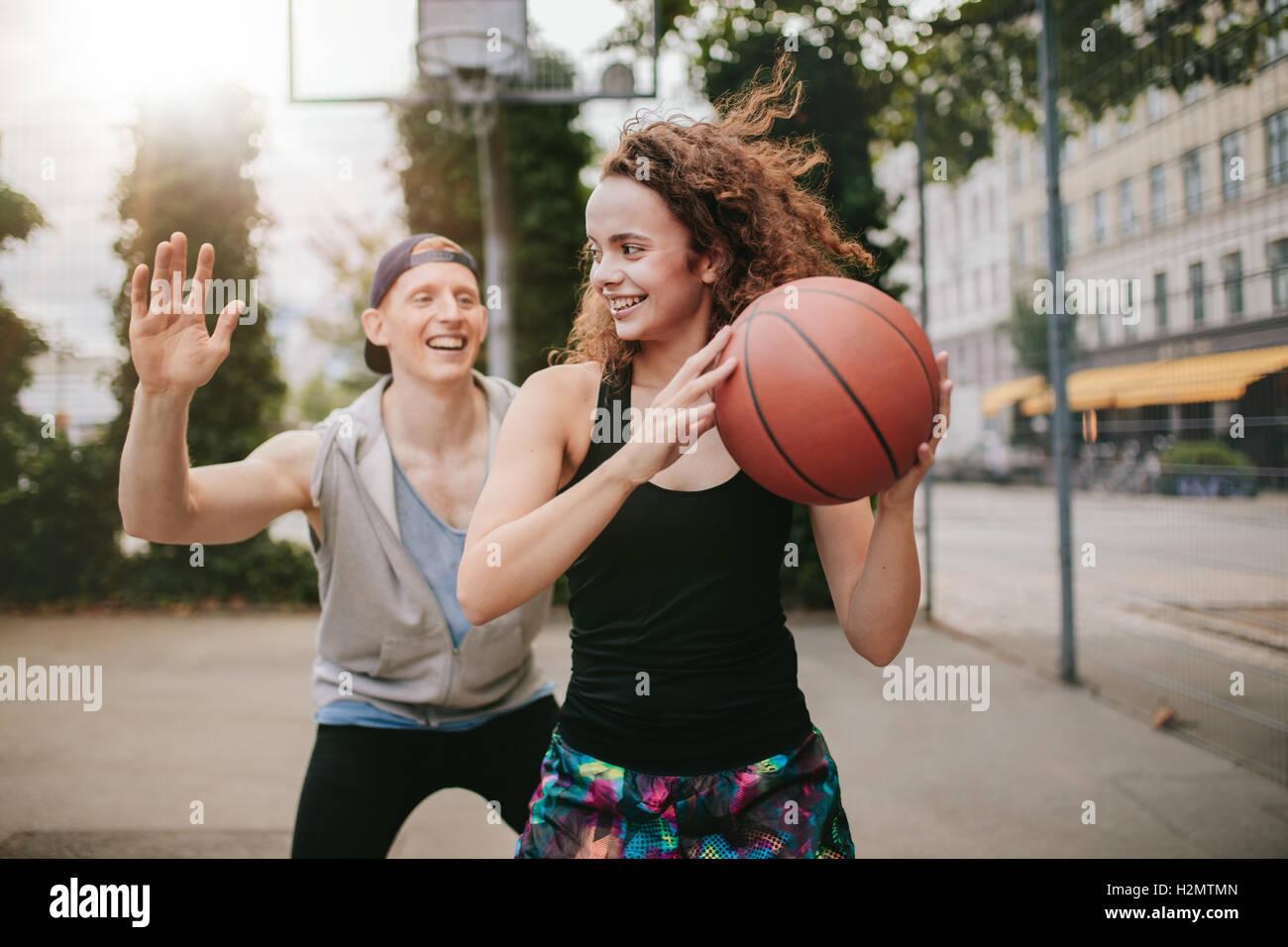 Niña jugando baloncesto con boy bloqueando. Amigos adolescentes disfruta de un juego de streetball en corte Imagen De Stock