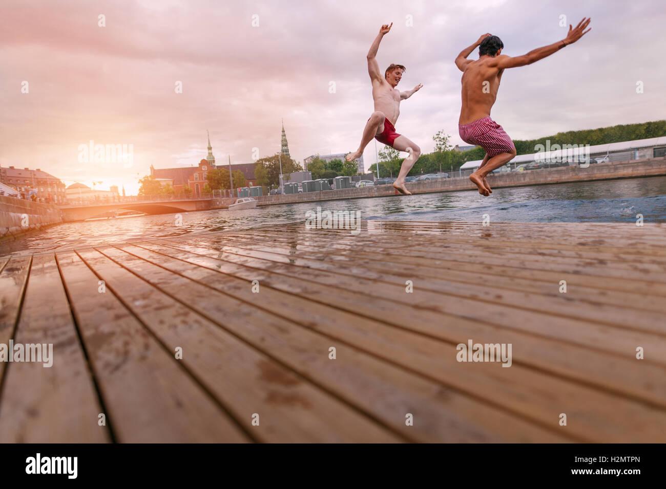 Los jóvenes saltando en el lago en la ciudad. Dos jóvenes amigos, disfrutando de un fin de semana. Imagen De Stock