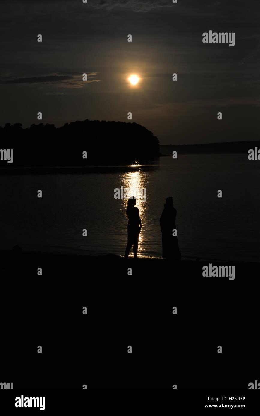 Tranquilidad, paz, dos mujeres de contorno en el fondo del lago Imagen De Stock