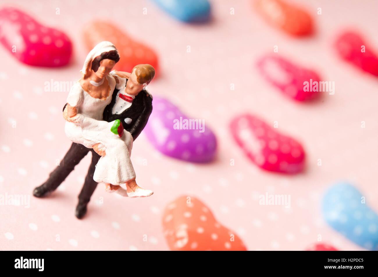 Figuras de la novia y el novio con corazones de San Valentín, el amor y el matrimonio concepto Imagen De Stock