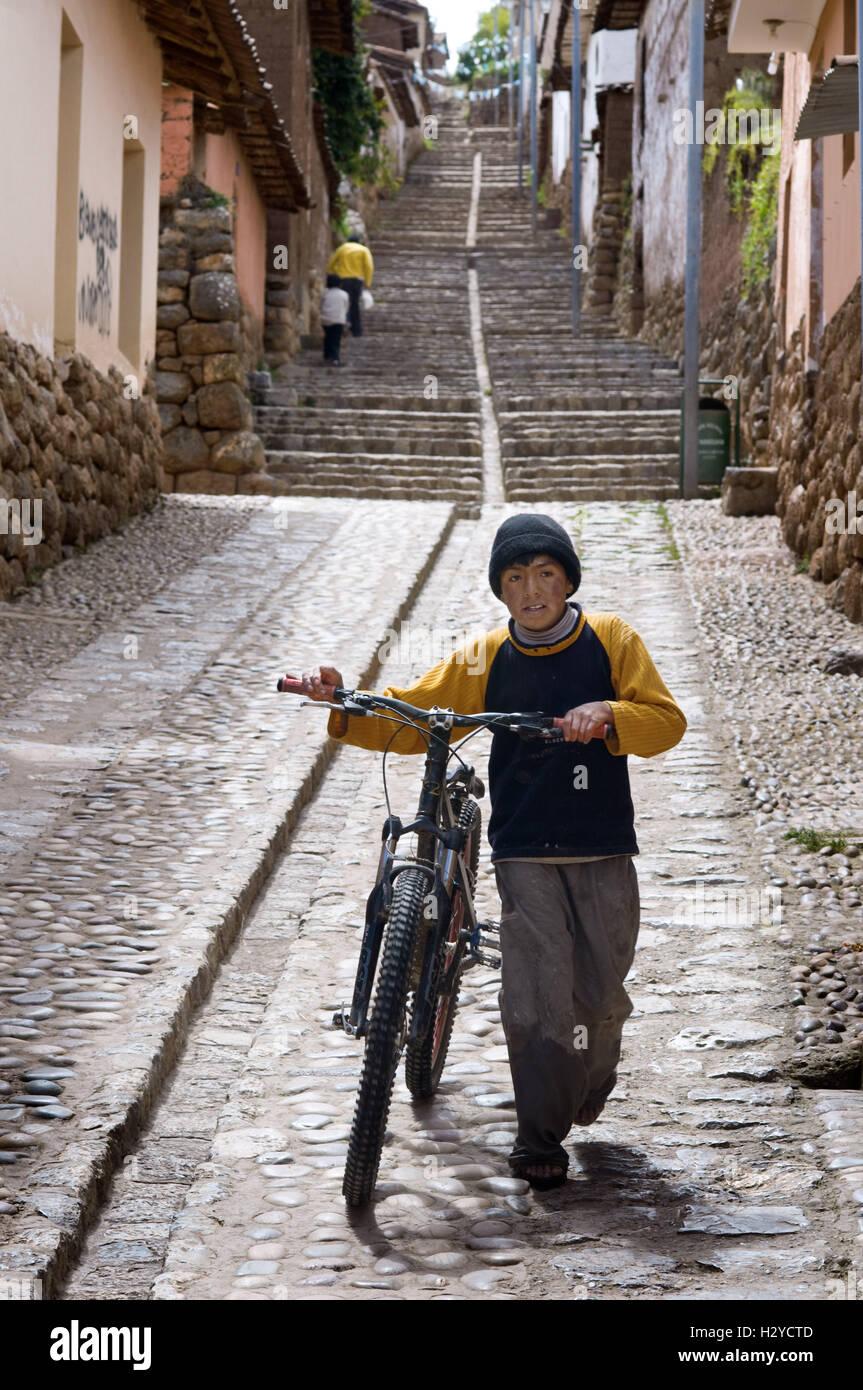 Un niño en una bicicleta en una de las empinadas calles de la pequeña aldea  de d366b762a11