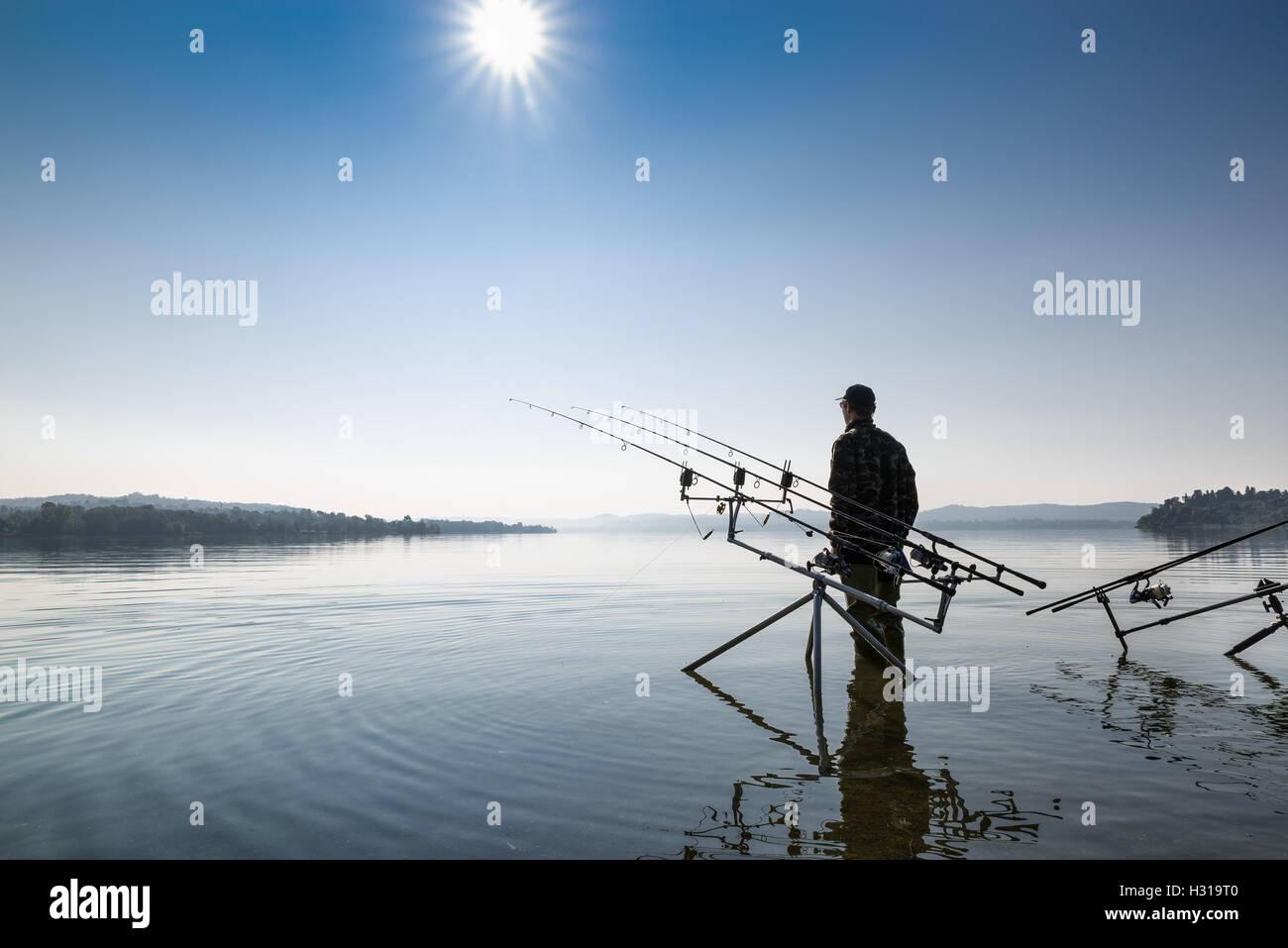 Aventuras de pesca. Pescador cerca del equipo carpfishing Imagen De Stock