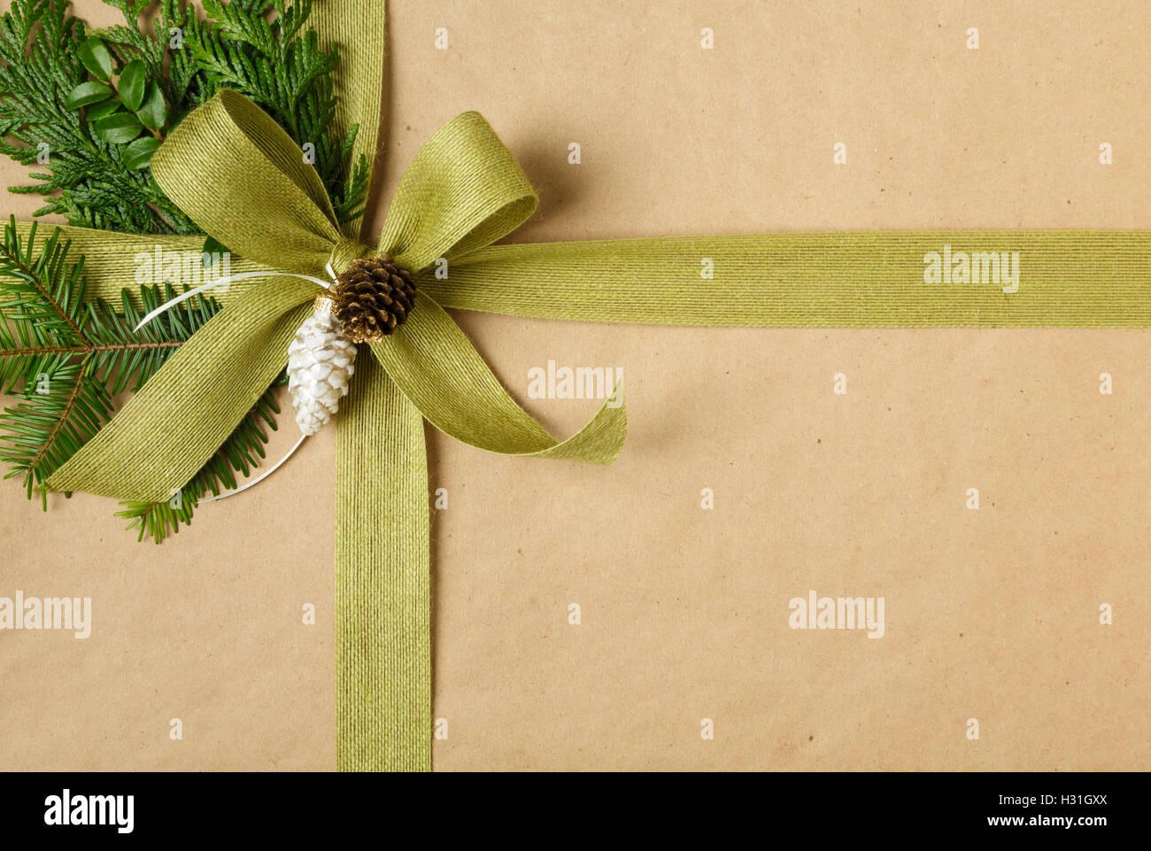 Cerca de proa y decoraciones naturales en su regalo de Navidad. Regalo de navidad envuelto en papel de embalaje Imagen De Stock