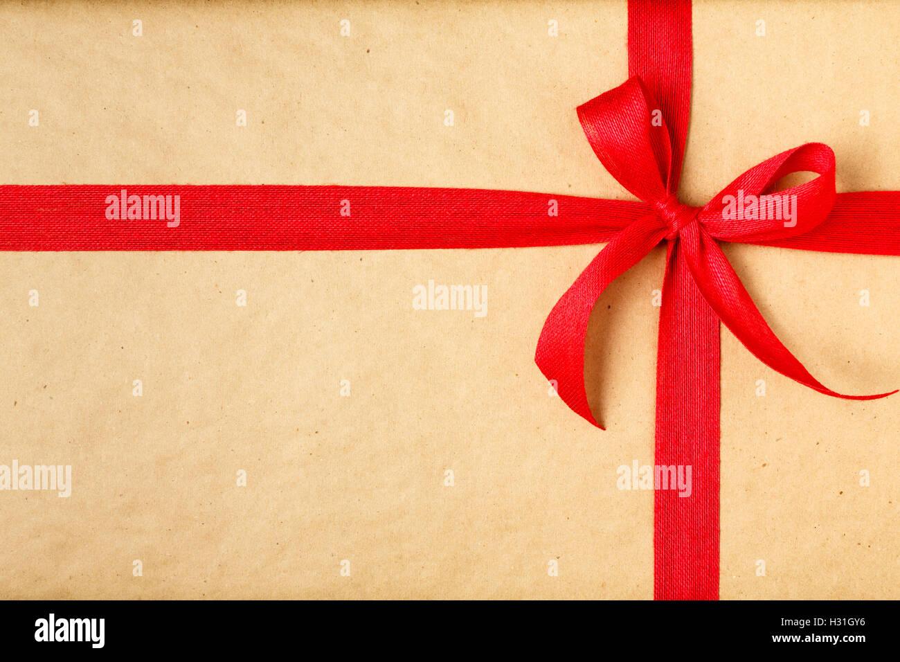 Regalo de Navidad Regalo de Navidad simple fondo con papel de embalaje reciclado y lazo rojo Imagen De Stock