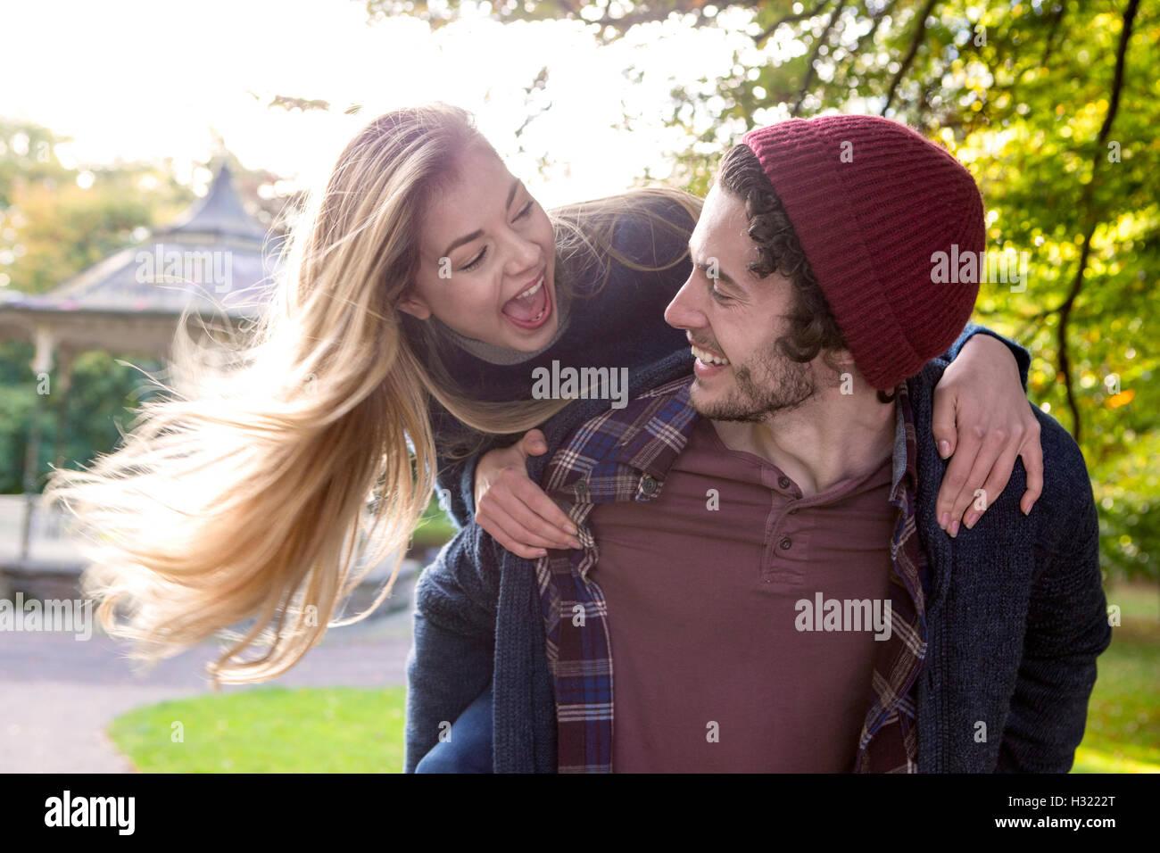 Pareja joven divirtiéndonos juntos al aire libre. El mans novia es saltar sobre su espalda. Imagen De Stock