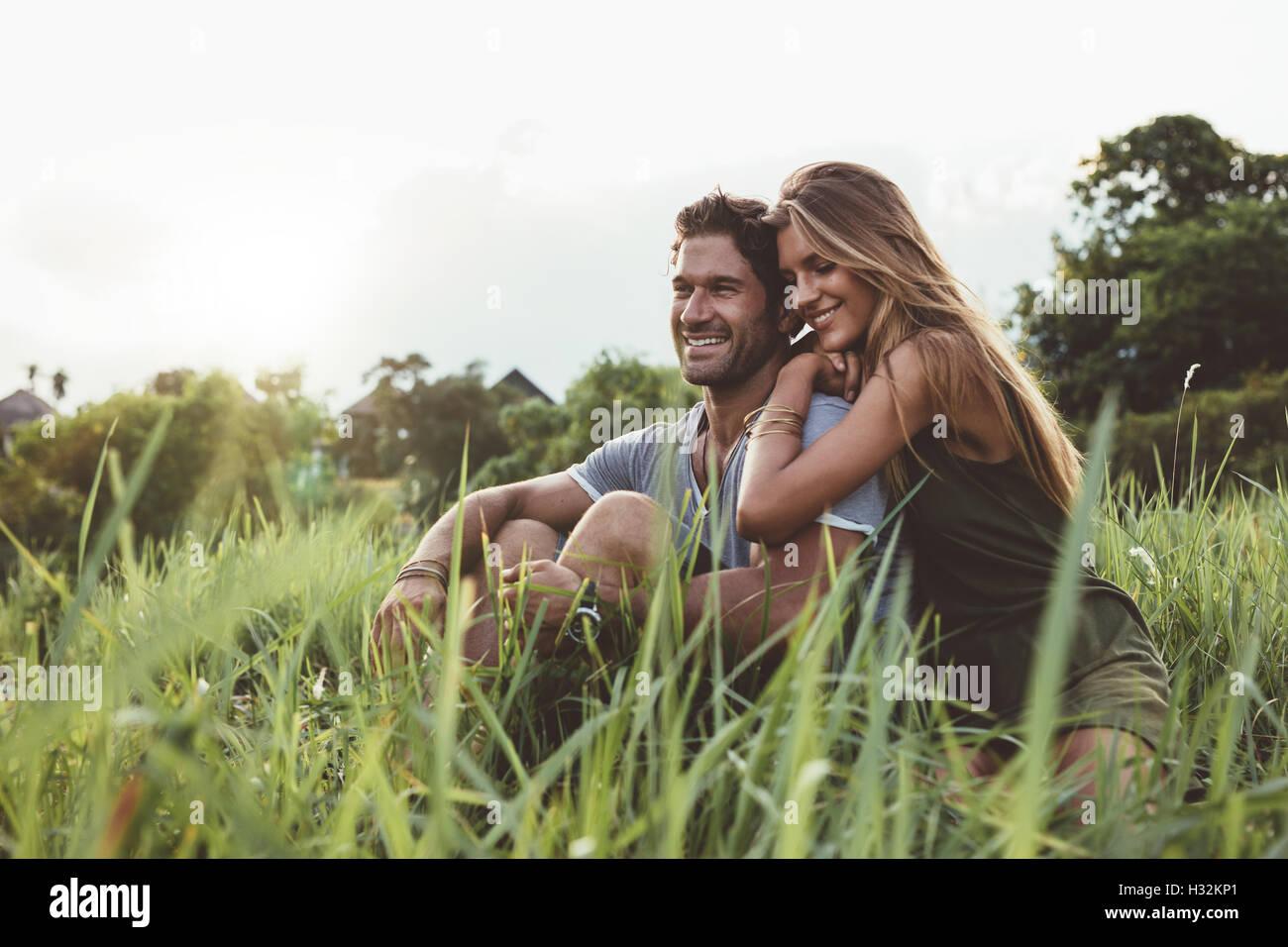 Disparó al aire libre de jóvenes amantes felices sentados en el prado. Feliz pareja joven en la hierba. Imagen De Stock