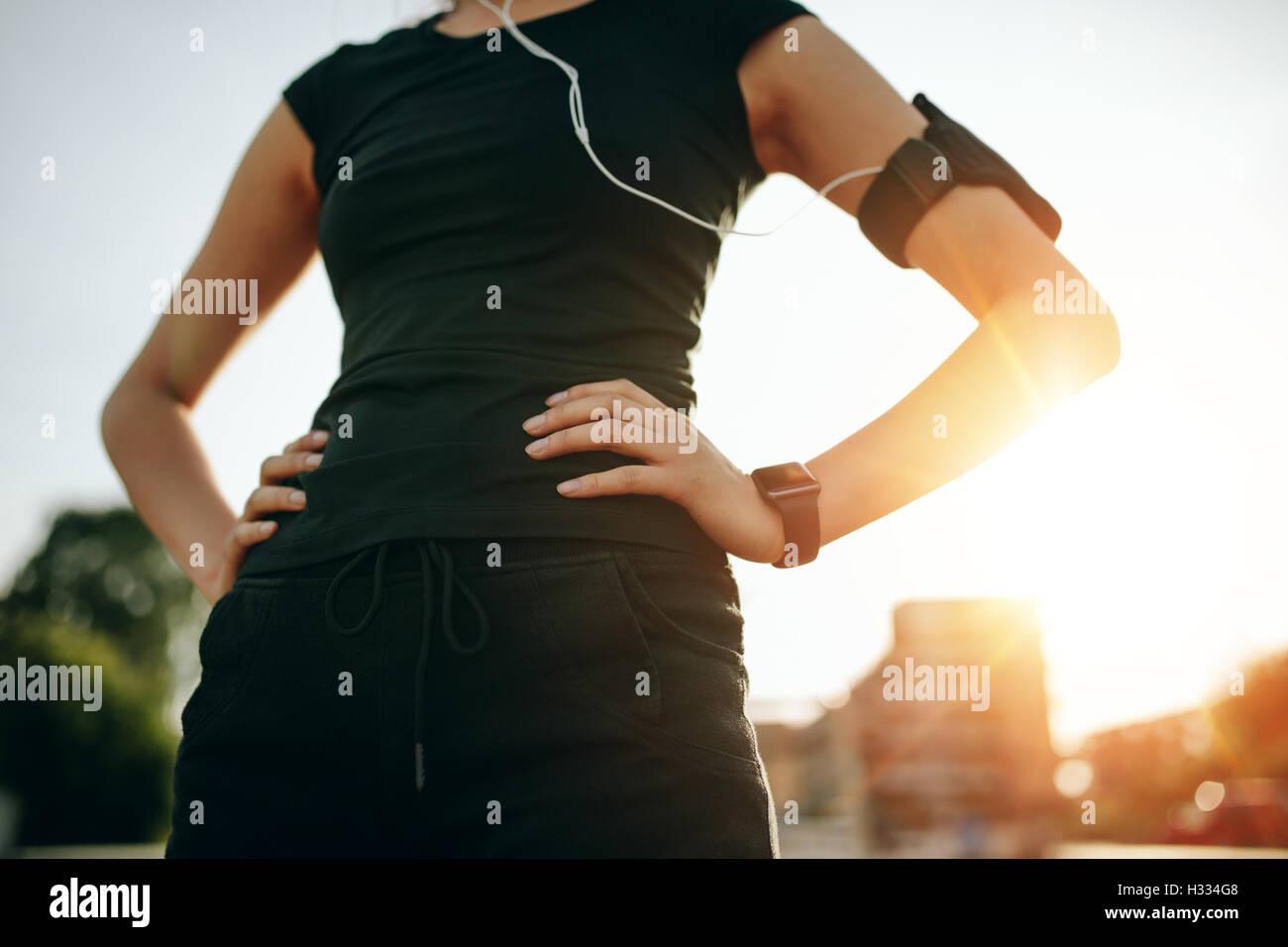 Captura recortada del monte joven de pie con las manos en las caderas. Urban runner afuera en el sol por la mañana. Imagen De Stock