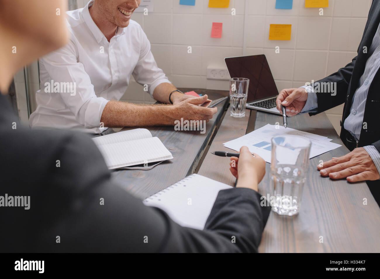 Cerca del empresario explicando un plan financiero a sus colegas en la reunión. Gente de negocios discutir un plan financiero alrededor Foto de stock