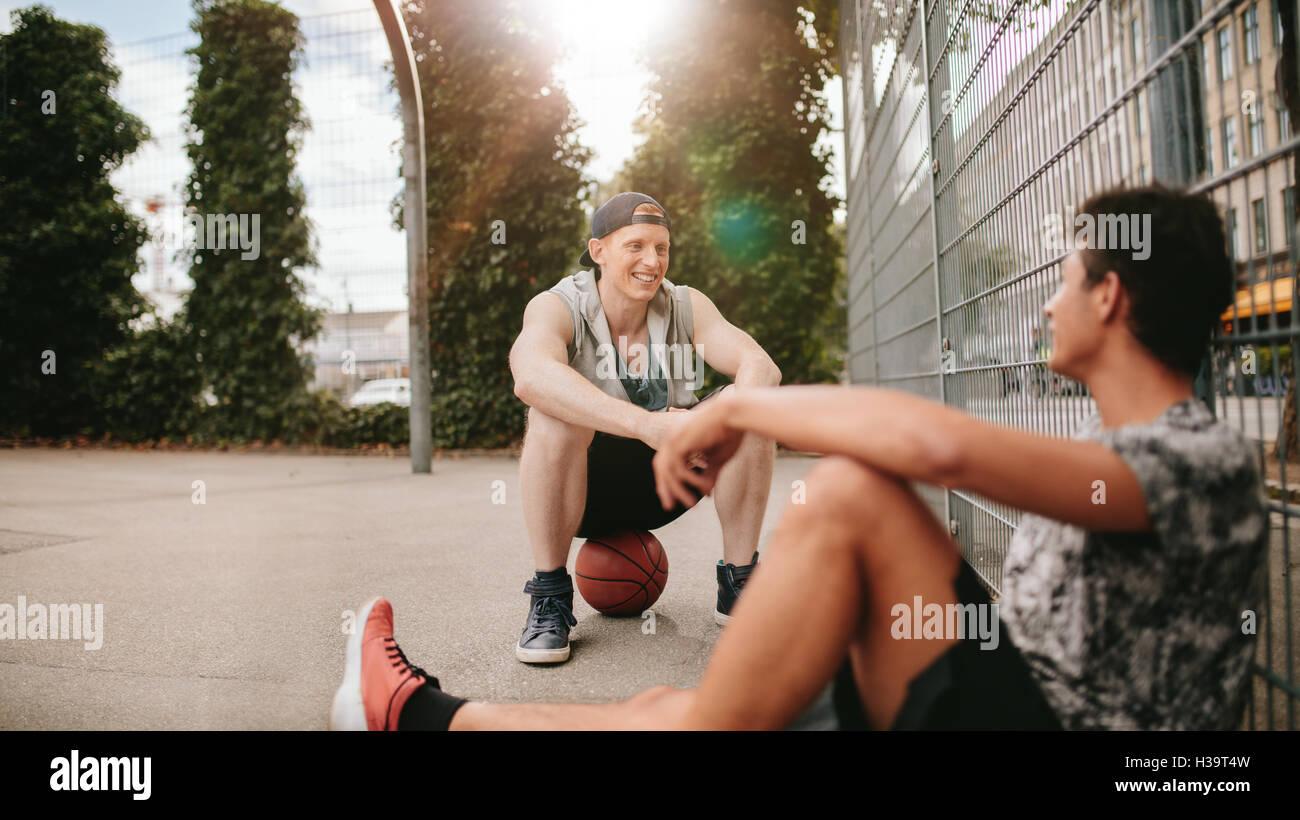 Jóvenes amigos sentados en la cancha de baloncesto. Los jugadores Streetball teniendo descanso después de un juego. Foto de stock