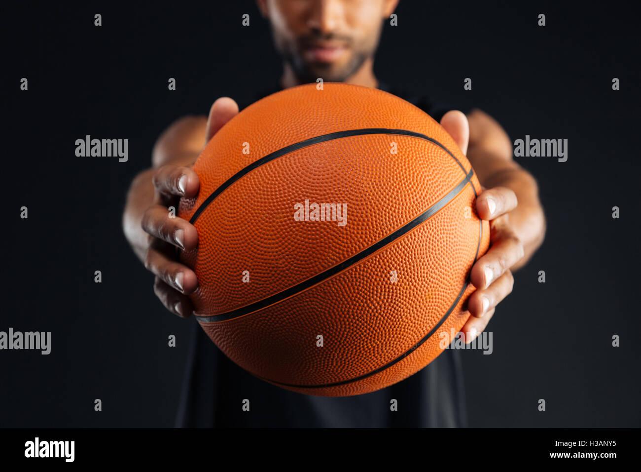 Imagen recortada de un joven jugador de baloncesto centrado africanos dando bola aislado en un fondo negro Imagen De Stock