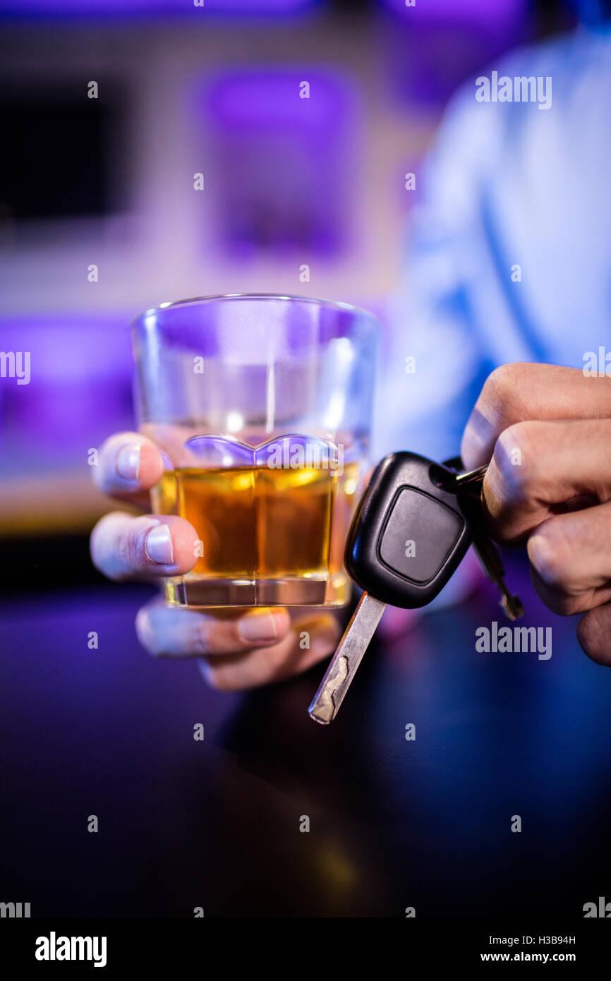 Hombre sujetando un vaso de whisky y las llaves del coche Foto de stock