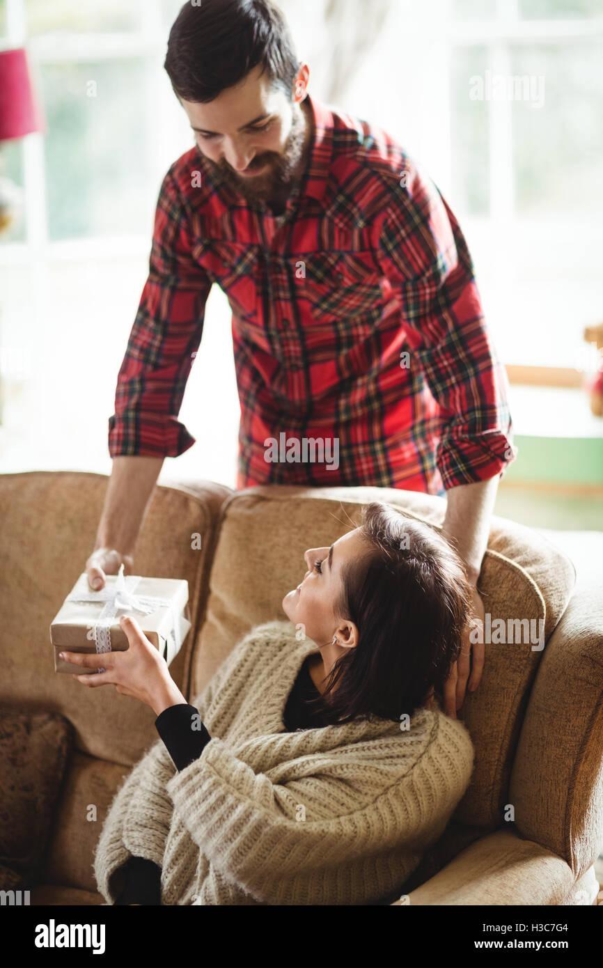 Hombre Mujer sorprendente con un regalo en el salón Imagen De Stock