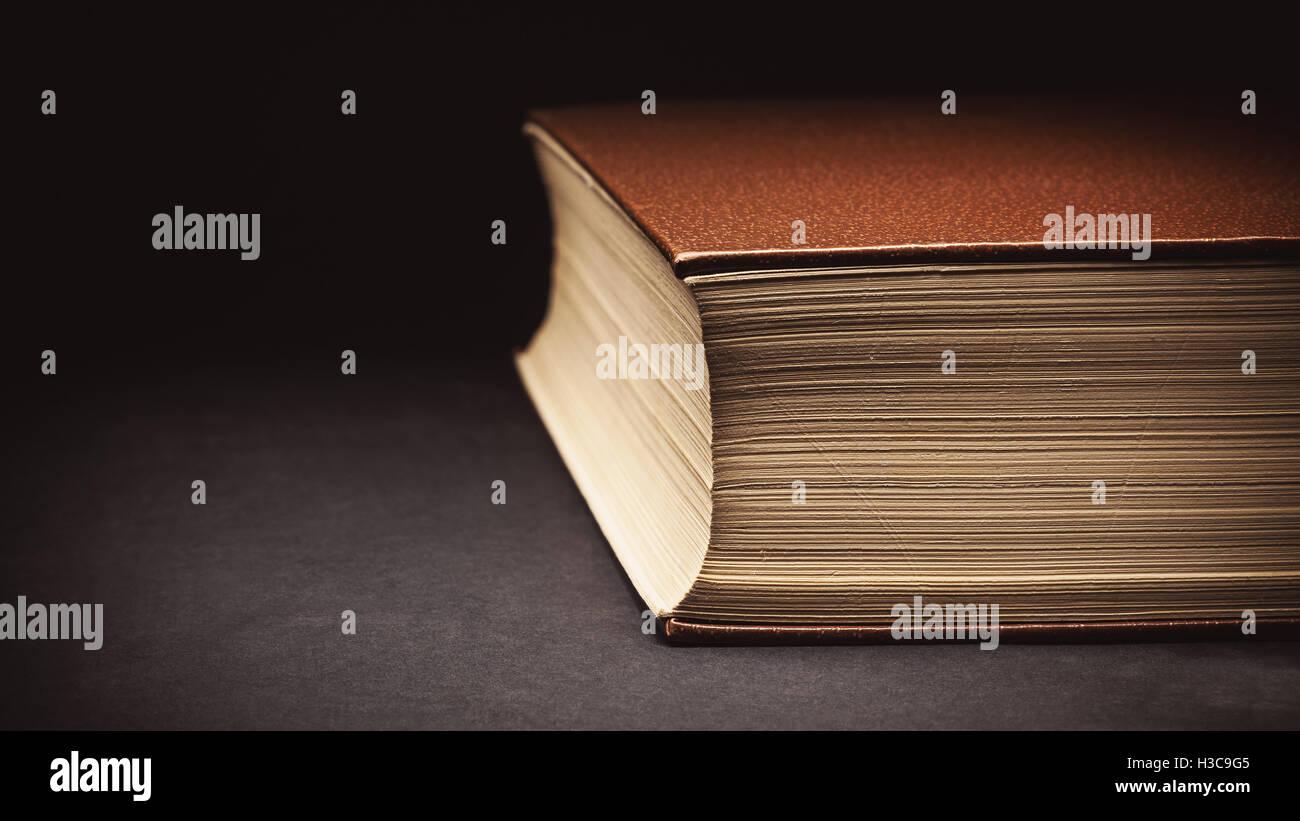 Acercamiento a un viejo libro cerrado, detalles de papel y una cubierta de cuero sintético. Imagen De Stock