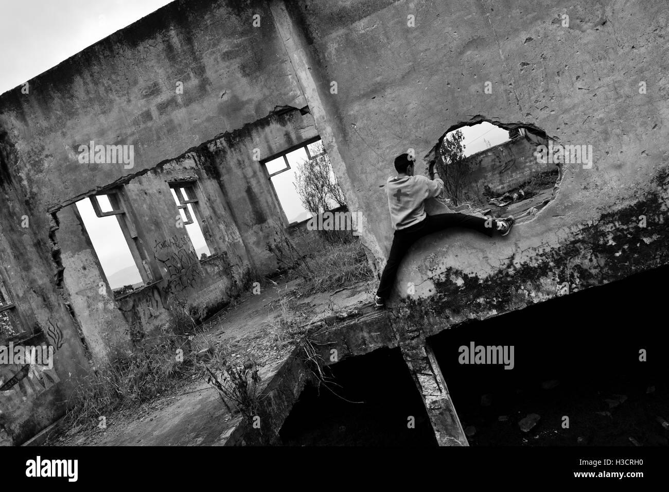 Un colombiano parkour runner trepa dentro de una casa en ruinas durante un funcionamiento libre de formación Imagen De Stock