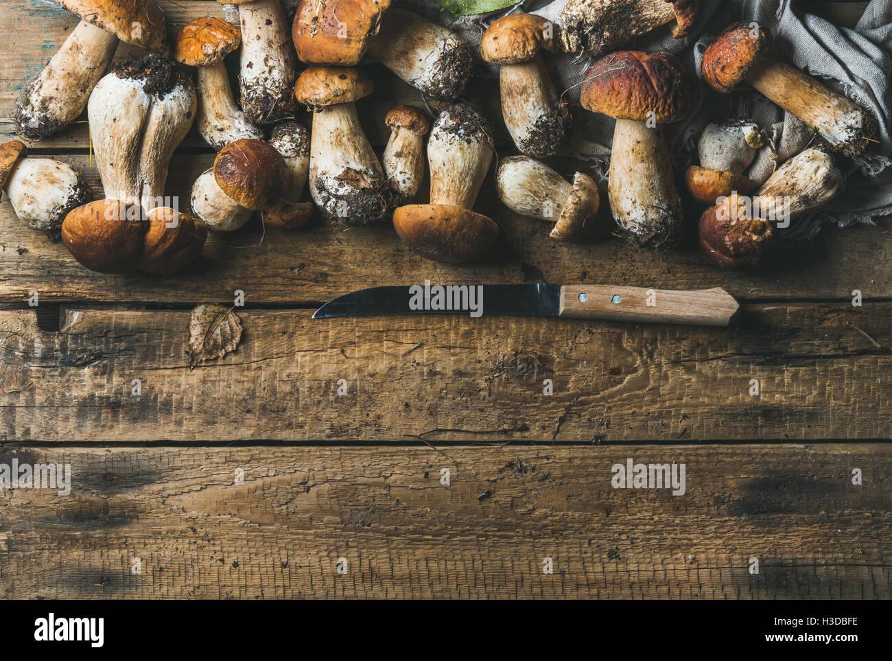 Setas blancas y cuchillo sobre fondo de madera rústica Imagen De Stock