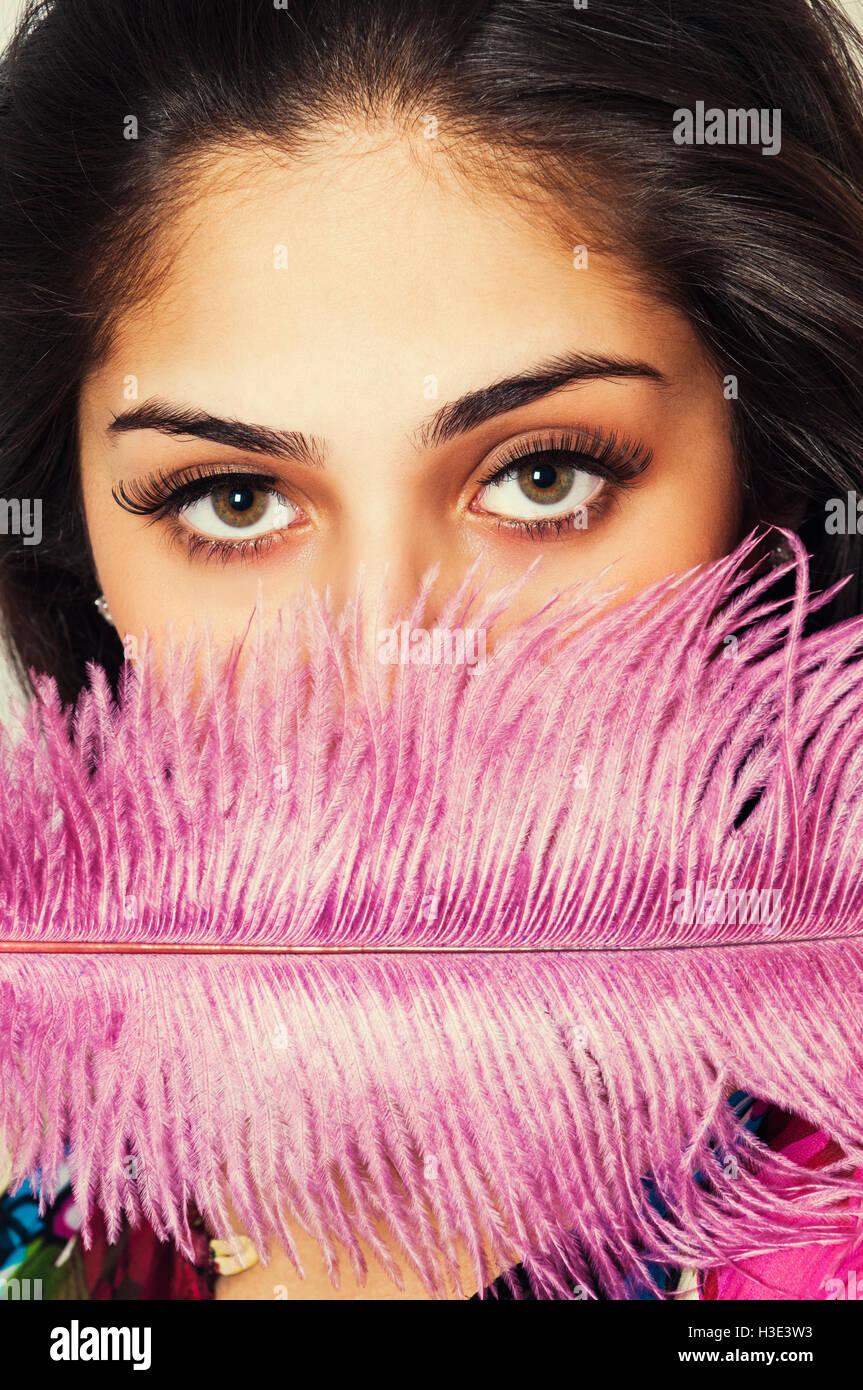 Hermosa joven ocultando la cara con pluma rosa Imagen De Stock