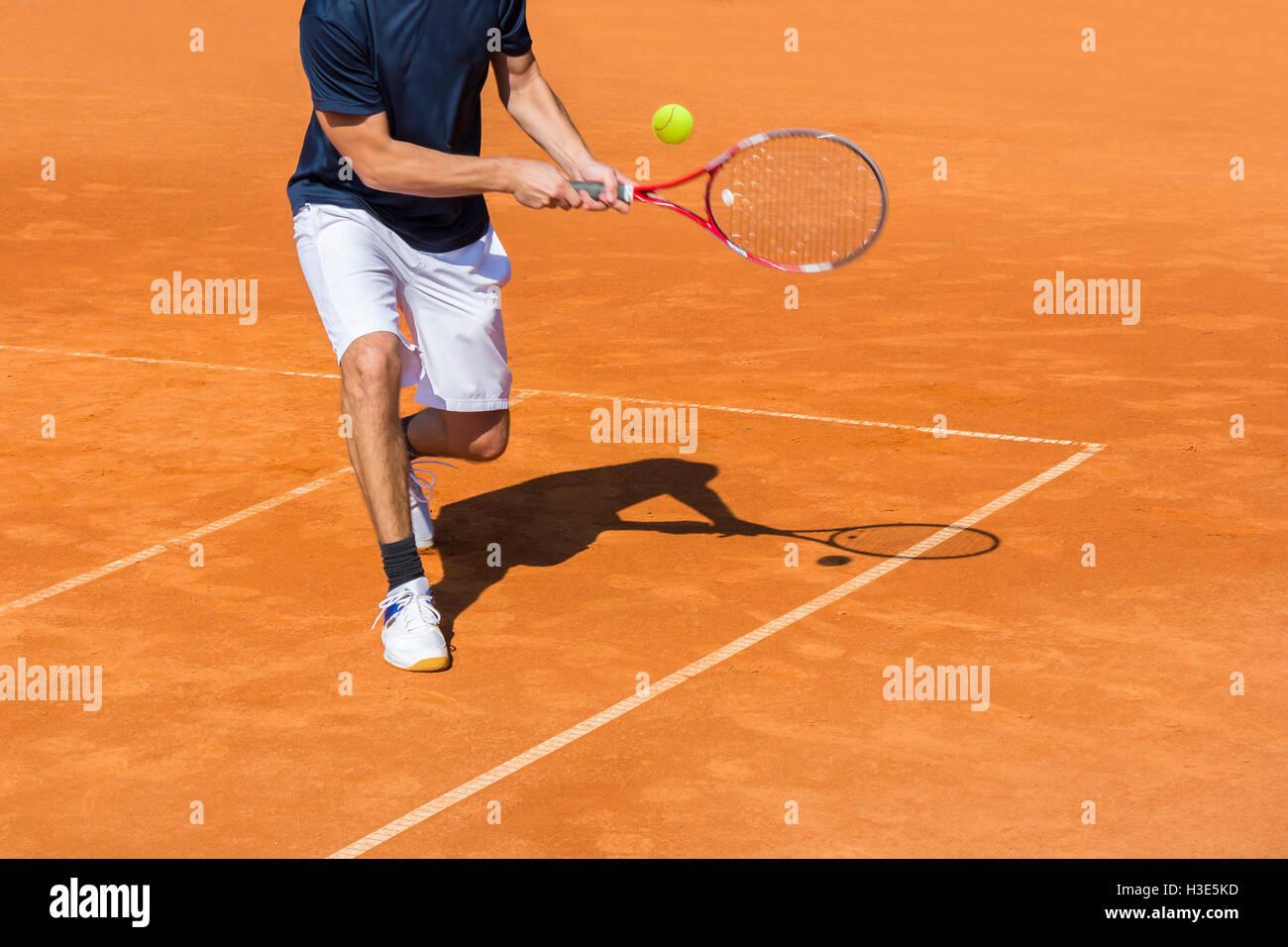 Jugador de tenis masculino en acción en la cancha de arcilla en un día soleado Imagen De Stock