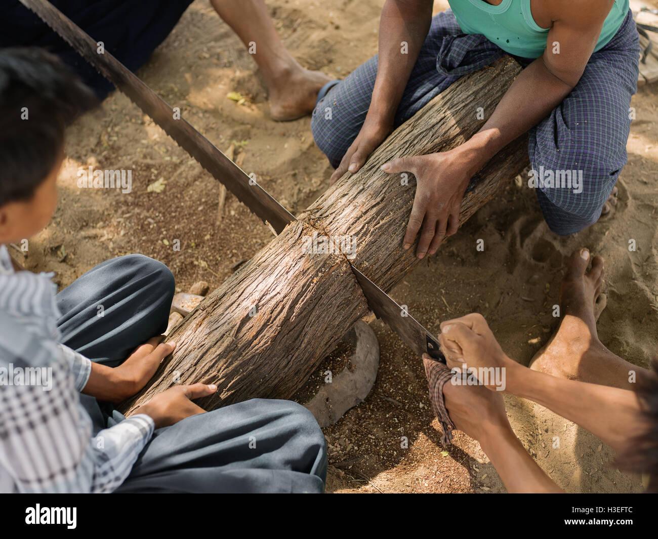 Un equipo de trabajadores a que se unan fuerzas para vio un registro en Myanmar (Birmania), Bagan Aldeas Foto de stock