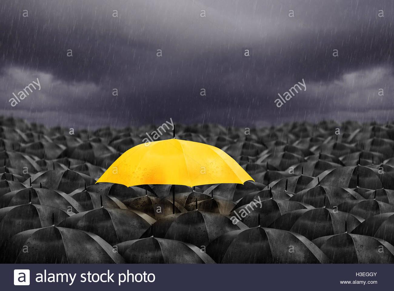 Paraguas amarillo en masa de Paraguas negro. Imagen De Stock